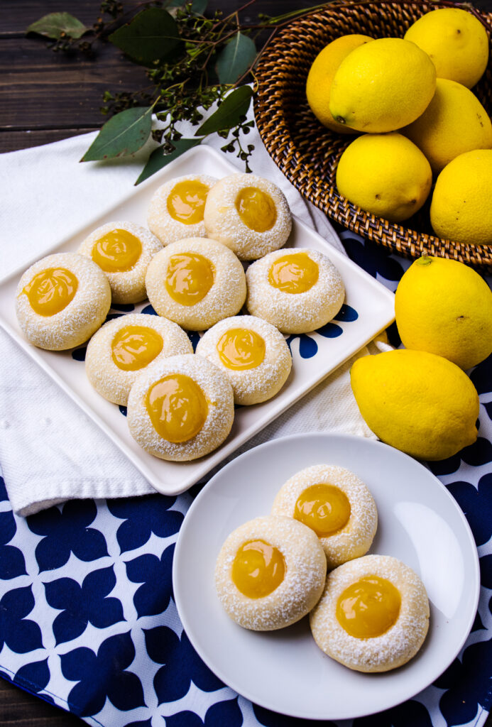 Lemon Curd Cookies on plates with lemons on the side.
