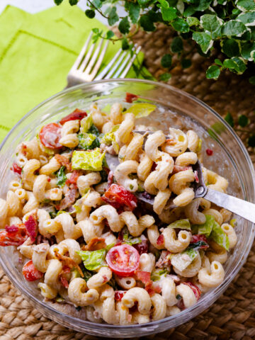 BLT Pasta Salad in a glass bowl served with a spoon.