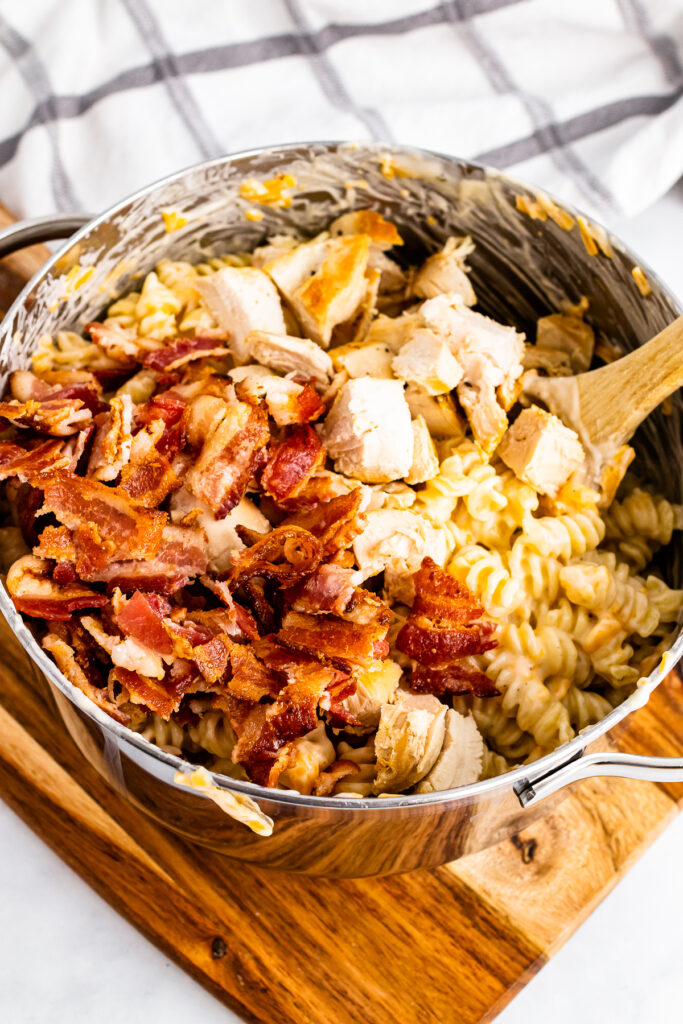 Bacon and pasta in a stock pot with chicken.