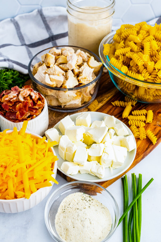 Ingredients of bacon, chicken, cheese, cream cheese, chives for recipe.
