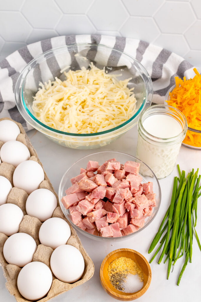 Eggs, cheese, hame and seasoning for Ham and Cheese Breakfast Casserole.