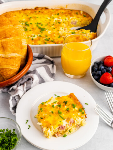 Ham and Cheese Breakfast Casserole slice on a white dish with a glass of orange juice.