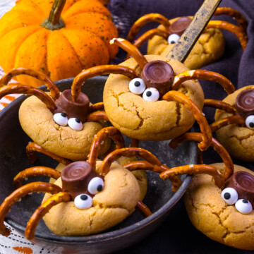 Spider Cookies in a ladle with pumpkins.