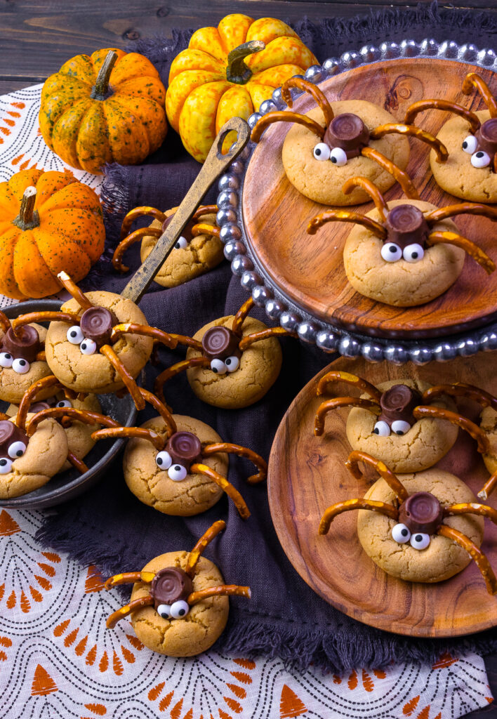 Spider Cookies on a cookie stand, a wooden plate and in a ladel with pumpkins
